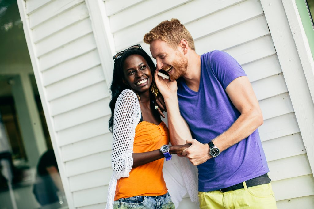 Young multiracial couple with mobile phone